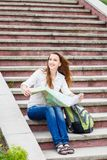 Jeune femme de déplacement s'asseyant avec la carte sur des escaliers Photographie stock libre de droits