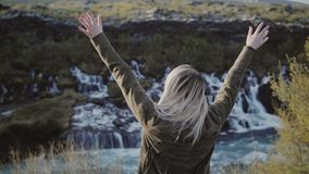 Jeune femme de déplacement se tenant près des cascades en Islande et le sourire Fille soulevant des mains et se sentant heureuse banque de vidéos