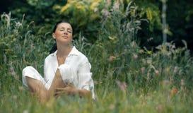 Jeune femme de détente s'asseyant dans l'herbe Photographie stock libre de droits