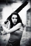 Jeune femme de danger avec le bâton Photos stock