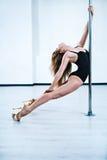 Jeune femme de danse de pôle Photographie stock libre de droits