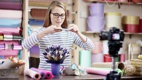 Jeune femme de fleuriste enveloppant des fleurs en papier au fleuriste faisant une leçon visuelle Elle essaye de composer les fle clips vidéos
