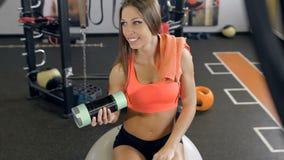 Jeune femme de forme physique avec la serviette et le dispositif trembleur souriant, elle s'assied sur la boule de pilates banque de vidéos