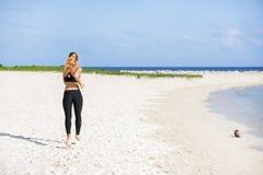 Jeune femme de forme physique courant à la plage Photo stock