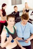 Jeune femme de forme physique faisant la rotation avec l'instructeur Image libre de droits