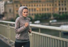 Jeune femme de forme physique pulsant dans la ville pluvieuse Image stock
