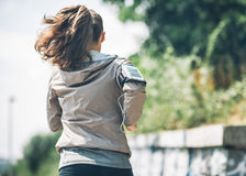 Jeune femme de forme physique pulsant en parc de ville Photo stock