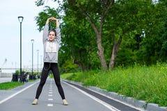 Jeune femme de forme physique s'étirant après course portrait de sport d'ext?rieur image libre de droits
