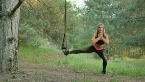 Jeune femme de forme physique s'étirant dans la forêt de pin Photographie stock