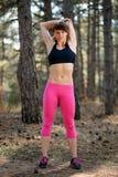 Jeune femme de forme physique s'étirant dans le pin Forest Female Runner Doing Stretches Concept sain de style de vie Photos stock