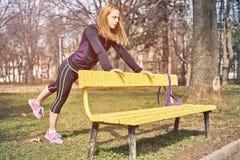 Jeune femme de forme physique s'exerçant en parc photos stock