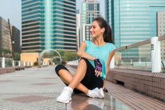 Jeune femme de forme physique se reposant après l'exercice, sourire, se reposant au banc au centre de la ville photos libres de droits