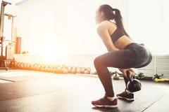 Jeune femme de forme physique soulevant la cloche lourde de bouilloire au gymnase images libres de droits