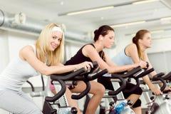 Jeune femme de forme physique sur la rotation de vélo de gymnastique Photographie stock