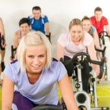 Jeune femme de forme physique sur la rotation de vélo de gymnastique Photographie stock libre de droits