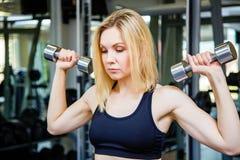 Jeune femme de forme physique tenant un poids de main Images stock