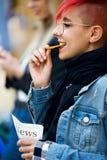 Jeune femme de hippie mangeant des pommes de terre tandis que son ami à l'aide du smartphone dans la rue Image stock
