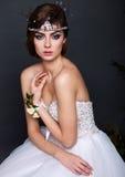Jeune femme de jeune mariée dans la robe de mariage sur le fond gris Image stock