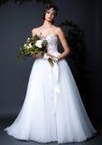 Jeune femme de jeune mariée dans la robe de mariage sur le fond gris Image libre de droits