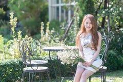 Jeune femme de l'Asie avec des fleurs se reposant sur la chaise en parc Images libres de droits