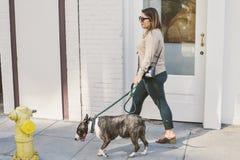 Jeune femme de Latina marchant son chien avec la bouche d'incendie image libre de droits