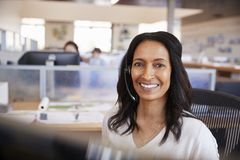 Jeune femme de métis à un centre d'appel regardant à l'appareil-photo image libre de droits