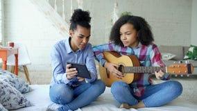 Jeune femme de métis avec la tablette se reposant sur le lit enseignant sa soeur adolescente à jouer la guitare acoustique à la m Photos libres de droits