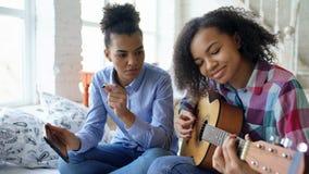 Jeune femme de métis avec la tablette se reposant sur le lit enseignant sa soeur adolescente à jouer la guitare acoustique à la m Photographie stock