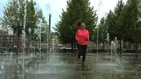 Jeune femme de métis courant sous la pluie près des fontaines de parc de ville, tir de mouvement lent clips vidéos
