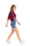 Jeune femme de marche dans la vue de côté de salopette Photos libres de droits