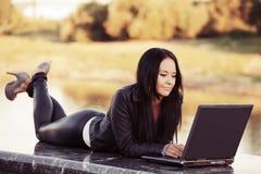 Jeune femme de mode à l'aide de l'ordinateur portable extérieur Photos stock