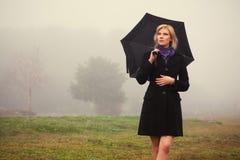 Jeune femme de mode avec le parapluie marchant dans un brouillard extérieur Photographie stock libre de droits