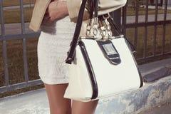 Jeune femme de mode avec le sac à main et la jupe de blanc Photo libre de droits