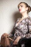 Jeune femme de mode avec le sac sur le papier peint images stock