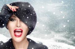 Jeune femme de mode d'hiver faisant des gestes avec le chapeau de fourrure jour neigeux Photographie stock