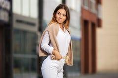 Jeune femme de mode dans la chemise blanche et des jeans déchirés marchant dans la rue de ville Photographie stock libre de droits