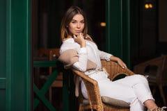 Jeune femme de mode dans la chemise blanche se reposant sur la chaise en osier Photos libres de droits