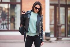 Jeune femme de mode dans la veste en cuir noire marchant dans la rue de ville Photo stock