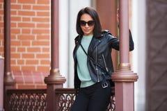 Jeune femme de mode dans la veste en cuir noire se penchant sur la balustrade Images libres de droits