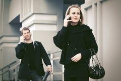 Jeune femme de mode dans le manteau noir parlant au téléphone portable Image libre de droits