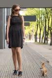 Jeune femme de mode, marchant son chien dans la rue Photographie stock