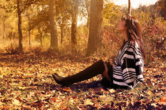 Jeune femme de mode s'asseyant dans des feuilles d'automne Image stock