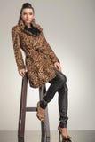 Jeune femme de mode s'asseyant sur un tabouret Photographie stock