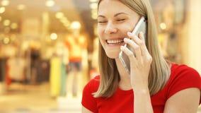 Jeune femme de mouvement lent s'asseyant dans le sourire de centre commercial Utilisant son smartphone, parlant avec des amis banque de vidéos