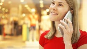 Jeune femme de mouvement lent s'asseyant dans le sourire de centre commercial Utilisant son smartphone, parlant avec des amis clips vidéos