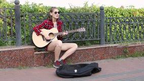 Jeune femme de musicien de rue jouant la guitare acoustique et chantant en parc de ville banque de vidéos