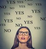 Jeune femme de pensée avec oui ou non le choix recherchant Photographie stock libre de droits