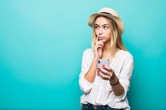 Jeune femme de pensée dans le chapeau de paille utilisant le téléphone portable d'isolement au-dessus du fond bleu images stock