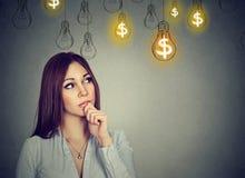 Jeune femme de pensée de portrait regardant les ampoules d'idée du dollar au-dessus de la tête images stock