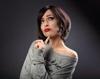Jeune femme de pensée sceptique avec le looki noir court de coiffure Image libre de droits